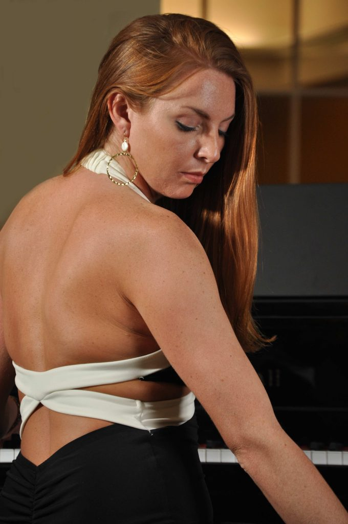 Beautiful red headed woman at grand piano looking down